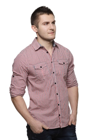 aside: Portrait of pensive young man standing with his hands in pockets looking sideways, isolated on white background