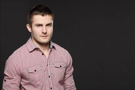 Closeup portrait of serious young handsome guy over dark background Stock Photo - 17411747