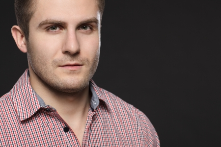 Closeup portrait of serious young handsome guy over dark background Stock Photo - 17411722
