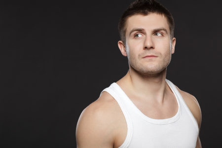 Closeup of handsome muscular man in white t-shirt over dark background photo