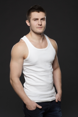 Young handsome muscular man in white t-shirt posing with his hands in pockets over dark background photo