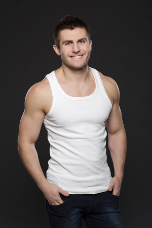 Young handsome muscular man in white t-shirt posing with his hands in pockets over dark background Stock Photo - 17411894