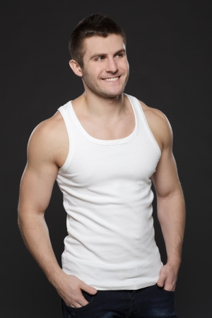 Young handsome muscular man in white t-shirt posing with his hands in pockets over dark background Stock Photo - 17411719