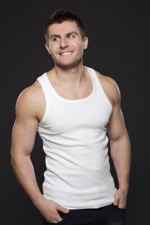 Young handsome muscular man in white t-shirt standing with his hands in pockets over dark background photo