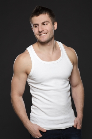 Young handsome muscular man in white t-shirt standing with his hands in pockets over dark background Stock Photo - 17411896