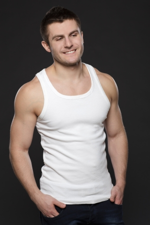Young handsome muscular man in white t-shirt standing with his hands in pockets over dark background Stock Photo - 17411898
