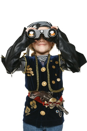 Six years girl wearing costume of pirate looking away through the binoculars at you, over white background photo