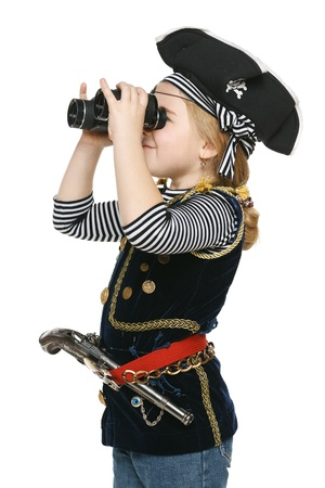 Six years girl wearing costume of pirate looking away through the binoculars, over white background