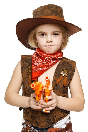 Angry little girl wearing cowboy costume holding guns pointing at camera, over white background photo