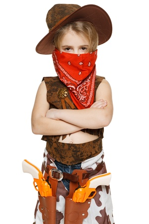 Little serious girl wearing cowboy costume and bandana covering her mouth standing with folded hands, over white background photo