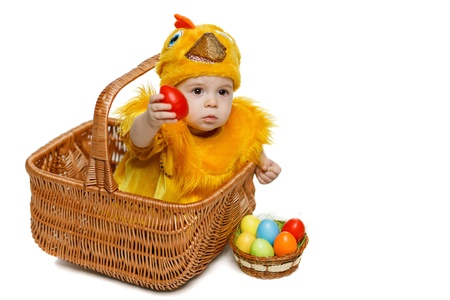 Baby sitting in Easter basket in chicken costume and giving you Easter egg, isolated on white background, with copy space  Easter holiday concept  photo