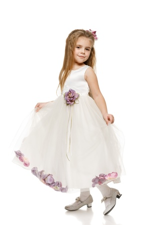 curtsy: Portrait of an adorable 6 years old girl in princess dress, over white background Stock Photo