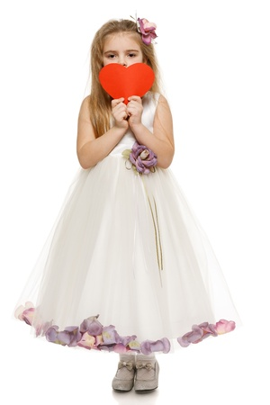 Adorable 6 years old girl in princess dress holding heart shape, over white background photo