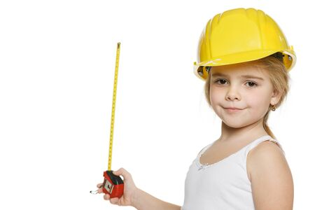 Little girl using a measuring tape over white background photo