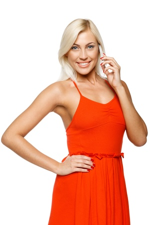 Smiling woman using cell phone looking at camera over white background