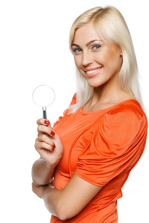 Happy woman in bright orange dress holding magnifying glass, over white background Stock Photo - 17537632
