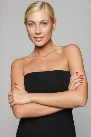 Mooie blonde glimlacht naar de camera met de armen over elkaar dragen van zwarte top over grijze achtergrond