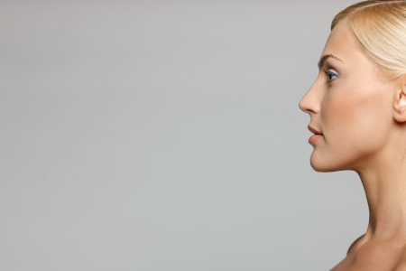 Cropped picture of side view closeup of beautiful blond woman looking forward over gray background photo