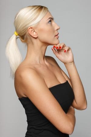 mujer pensativa: Vista lateral de la hermosa mujer rubia pensativa con la mano en la barbilla, lookinf arriba sobre fondo gris