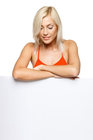 Smiling woman standing behind and leaning on a white blank billboard   placard, looking down at banner, over white background Stock Photo - 17537547