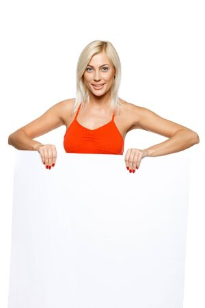 Smiling woman standing behind and holding a white blank billboard   placard, over white background Stock Photo - 17537515