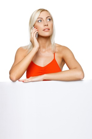 Concentrated woman standing behind and leaning on a white blank billboard   placard, talking on cellphone, looking away, over white background Stock Photo - 17537561