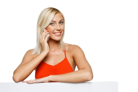 female elbow: Smiling woman standing behind and leaning on a white blank billboard   placard, talking on cellphone, looking at camera, over white background Stock Photo