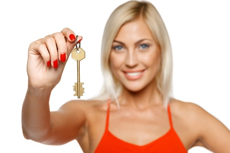 Closeup portrait of pretty young lady giving you a key, focus on the key, isolated on white background photo