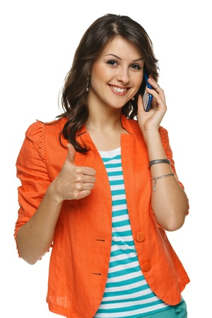 Bright picture of young woman talking on cellphone showing thumb up sign, over white background photo