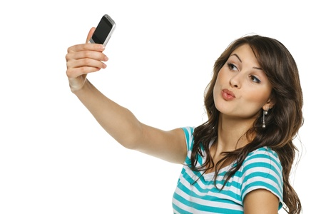Happy young girl making funny face while taking pictures of herself through cellphone, over white background photo