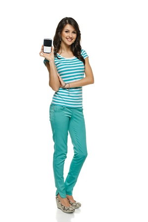 Young woman in full length showing her mobile phone, over white background