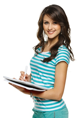 College university student woman making notes in the notebook, over white background photo