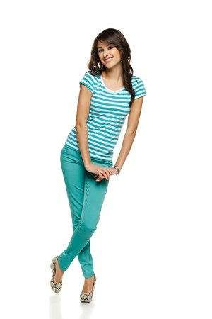 Full length of young flirty female in turquoise pants and t-shirt, over white background Stock Photo - 17537473