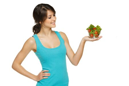 Beautiful woman holding transparent bowl with healthy salad meal, looking at bowl, over white, with copy space Stock Photo - 17537582