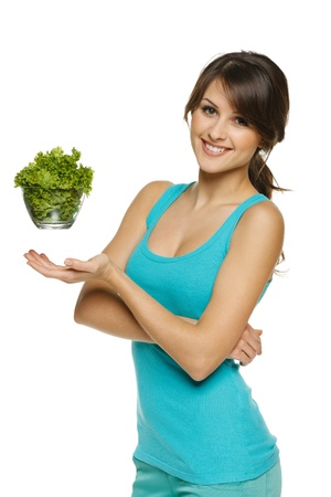 levitation: Light food concept  Smiling woman balancing lettuce leaves in transparent bowl, over white