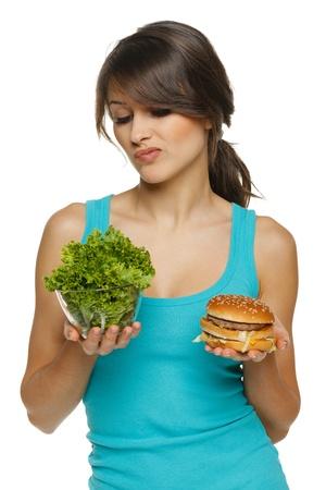 toma de decision: Dudando mujer la toma de decisiones entre la ensalada sana y comida rápida, sobre fondo blanco