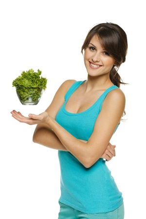 Light food concept  Smiling woman balancing lettuce leaves in transparent bowl, over white