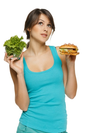 Pensive woman making decision between healthy salad and fast food, over white background