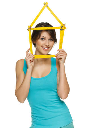 Happy woman looking through the house frame, over white background photo