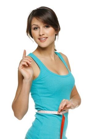 Beautiful woman measuring her waist with a measuring tape with finger up, over white background photo