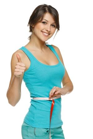 cintura: Mujer hermosa que mide su cintura con una cinta m�trica y muestra el pulgar hacia arriba, sobre fondo blanco