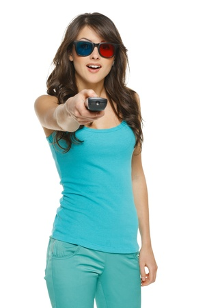 Surprised young woman with TV remote over white background photo
