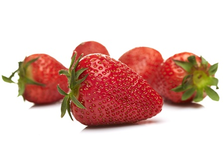 Fresh strawberries isolated on white background  Shallow depth of field  Focus at the first one  photo