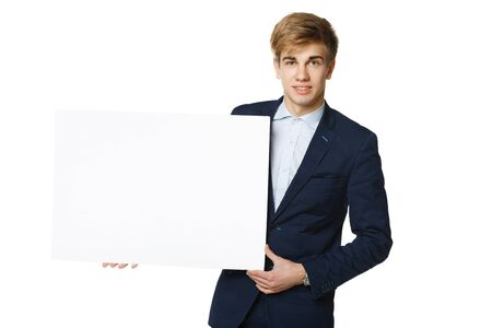 Young handsome man in suit holding blank whiteboard, over white background Stock Photo - 17786572