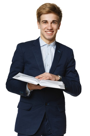 Young smiling man reading the book, over white background photo
