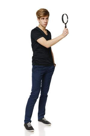 lupe: Young trendy man in full length looking trough the magnifying glass, over white background