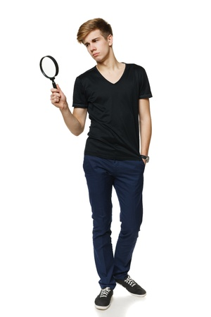 Young trendy man in full length looking trough the magnifying glass, over white background Stock Photo - 17786577