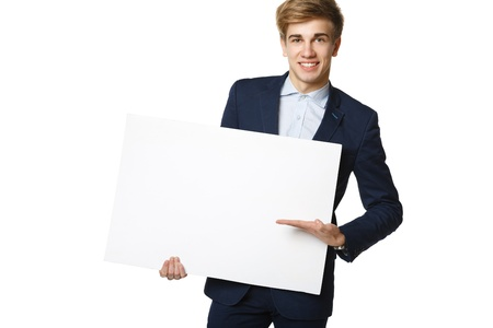 Young handsome man in suit holding blank whiteboard, over white background photo