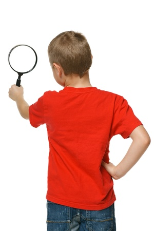 schoolkid search: Back viev of 6 years boy looking through the magnifying glass over white background