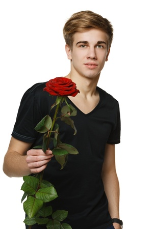 Young hansome man giving you red rose, over white background photo